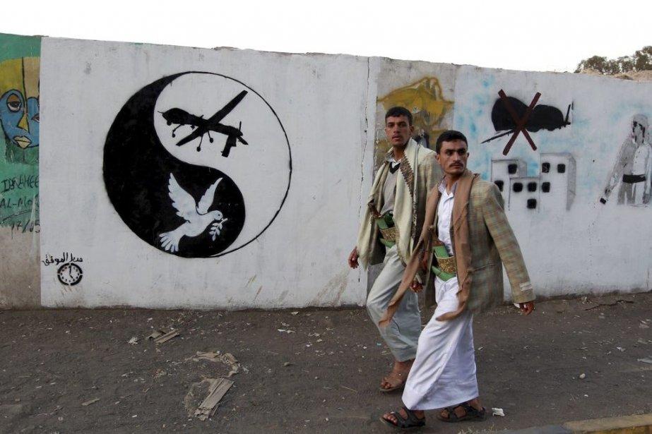 Deux hommes passent devant des graffitis représentants des... (PHOTO MOHAMMED HUWAIS, AFP)