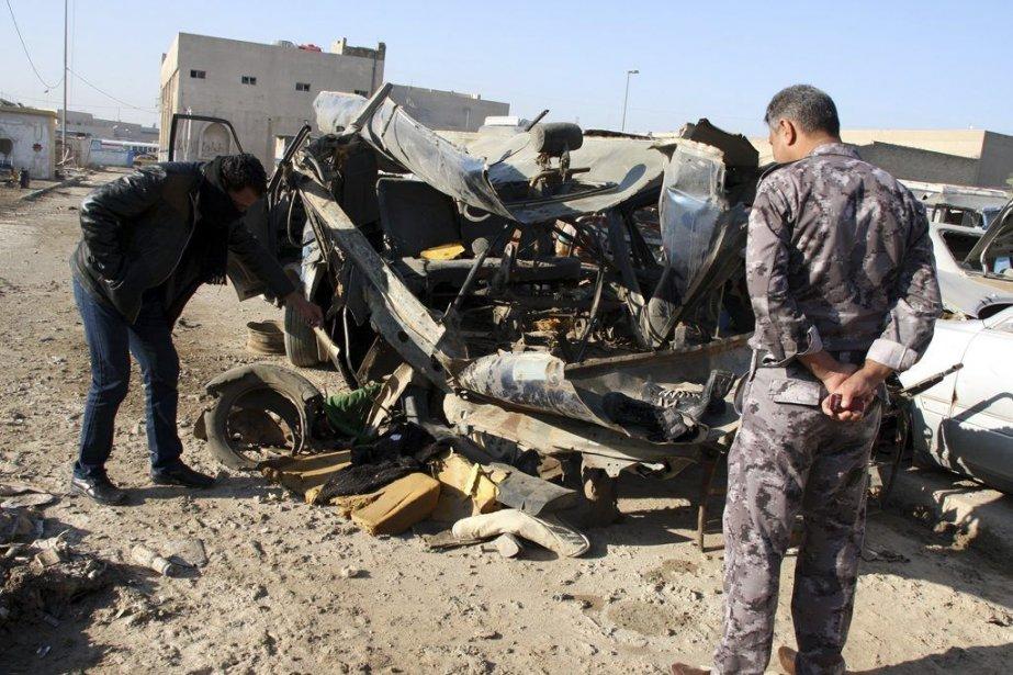 Des policiers examinent la carcasse d'une voiture ayant... (PHOTO REUTERS)