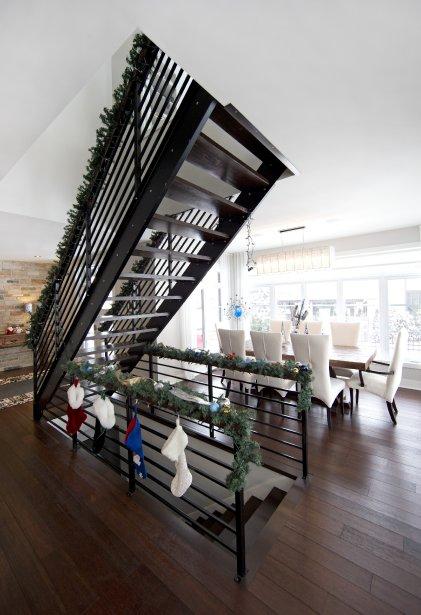 L'escalier en acier et en bois ne comprend pas de contremarches afin de laisser passer la lumière. La salle à manger a son pendant à l'extérieur, où l'on a installé un système de chauffage pour jouir le plus longtemps possible des repas pris à l'extérieur. (Photo Robert Skinner, La Presse)