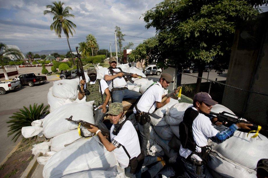 Les membres du groupe d'autodéfense de Michoacan patrouillent à bord d'un camion protégé par des sacs de sable. ()