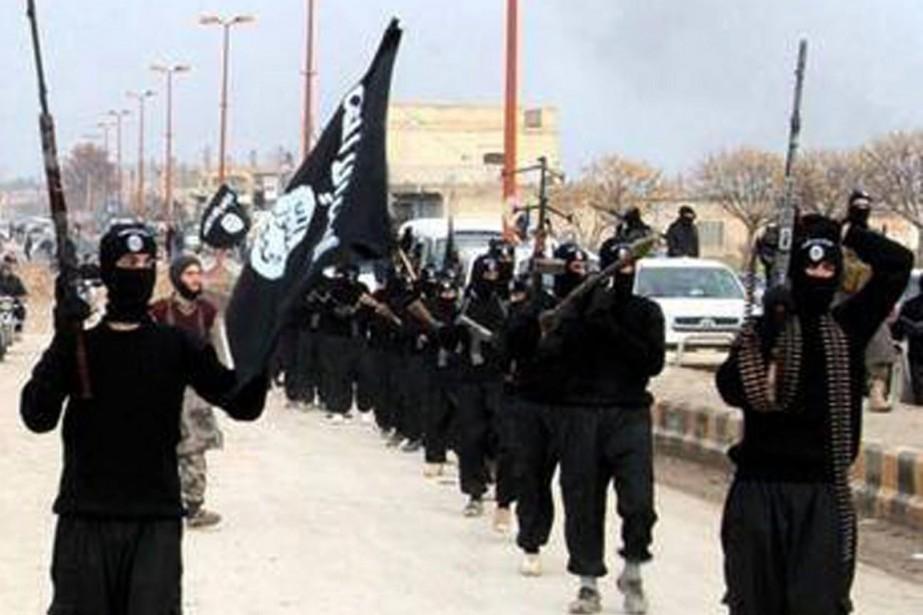 Un défilé de combattants d'EIIL à Raqqa, dans... (PHOTO ARCHIVES AP)