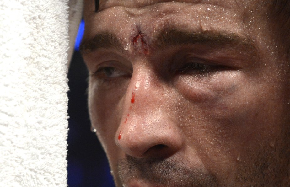 Lucian Bute, le visage tuméfié, regarde vers son soigneur. (Photo Bernard Brault, La Presse)