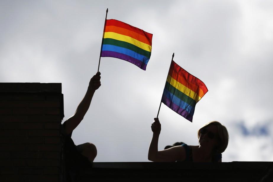 Des personnes brandissent le drapeau gai lors de... (Photo Mark Clinch, Reuters)