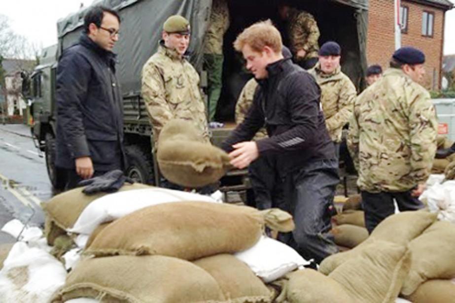 Le prince Harry aidant des militaires à décharger... (PHOTO ROBERT BOOTH/THE GUARDIAN)
