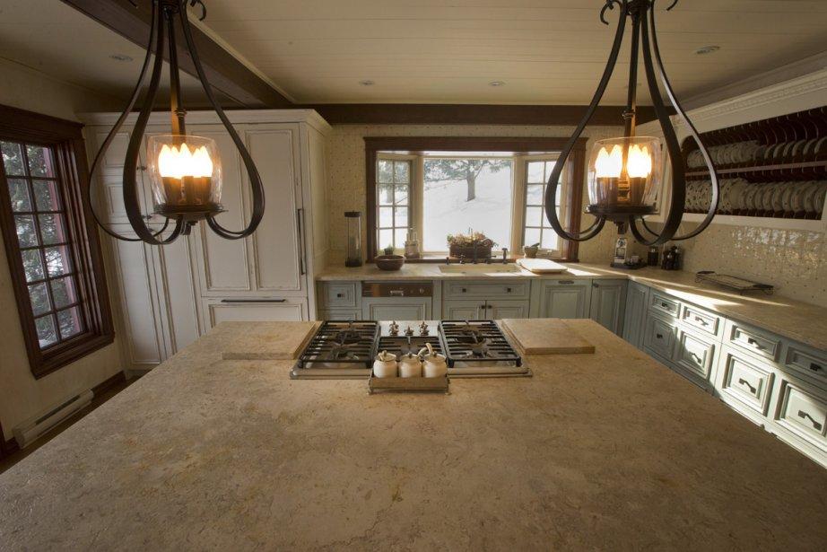 La cuisine est la pièce qui a subi le plus de transformations: on l'a éclaircie et rendue plus fonctionnelle, car Madame est une cuisinière motivée. Un généreux plan de travail est recouvert d'une pierre de Jérusalem. À gauche de la fenêtre, derrière des portes en bois à l'ancienne, se cache un frigo ultramoderne. (Photo Ivanoh Demers, La Presse)