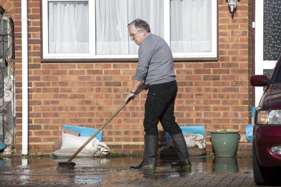 Un homme élimine l'eau accumulée dans son entrée,... (PHOTO NEIL HALL, REUTERS)