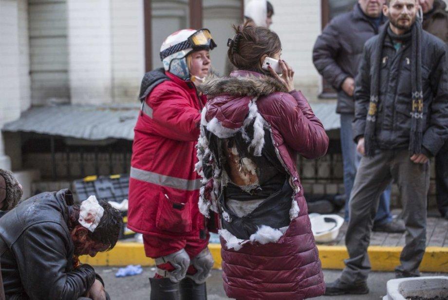Plus tôt dans la journée de mardi, des personnes blessées après des affrontements avec la police. Le manteau et les vêtements de cette femme, sont déchirés.   18 février 2014