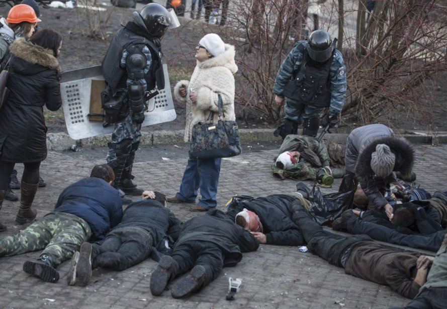 Des policiers anti-émeute se tiennent près de blessés, à terre, après des affrontements, lundi.   18 février 2014