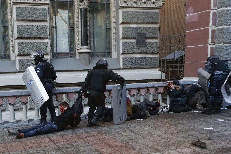La police anti-émeute détient des manifestants blessés après les affrontements dans le centre de Kiev, mardi.   18 février 2014