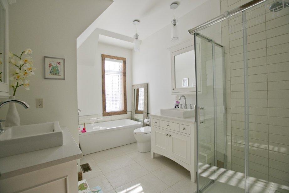 On a une drôle d'impression dans cette pièce où la baignoire a l'air petite à côté d'une cabine dans laquelle toute la famille peut se laver en même temps, puisqu'il y a trois robinets différents et autant de douchettes! (Photo David Boily, La Presse)