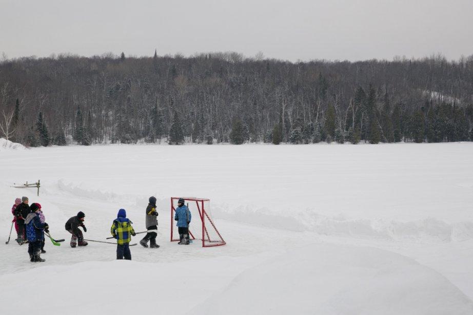Des enfants jouent au hockey sur le lac Claire, dans un décor naturel magnifique. (Photo David Boily, La Presse)
