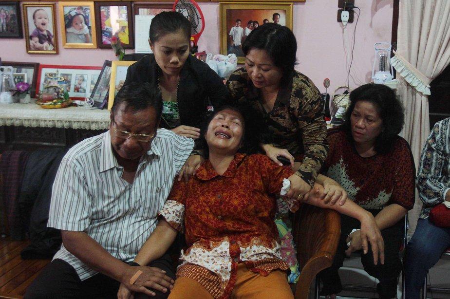 La famille de l'un des passagers de l'avion... (Photo AFP)