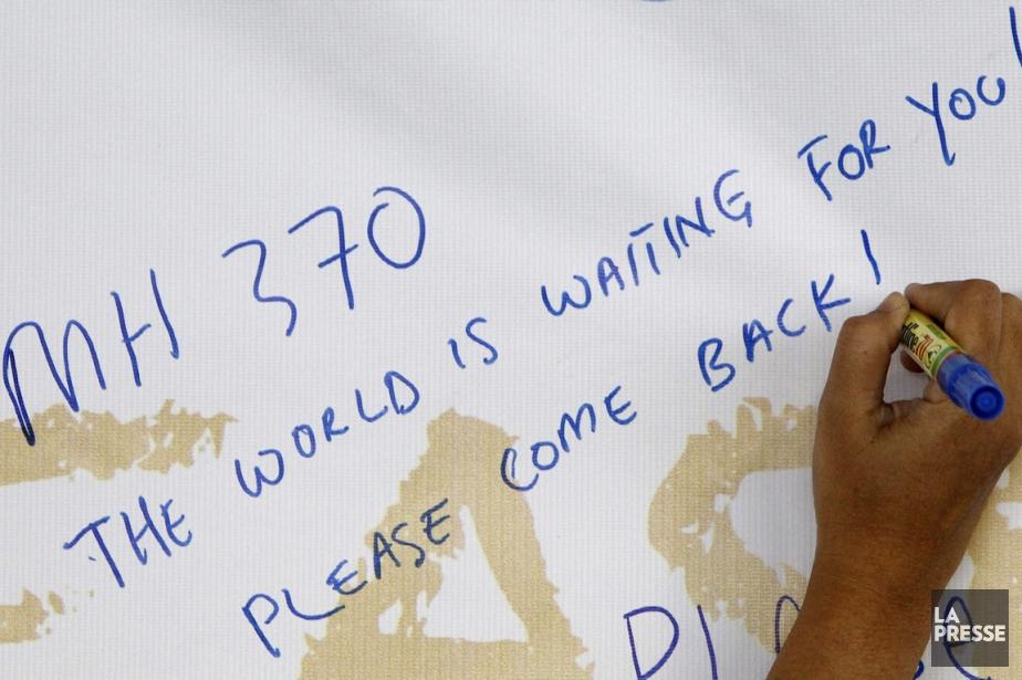 Une femme écrit un message d'encouragement à l'intention... (PHOTO LAI SENG SIN, AP)