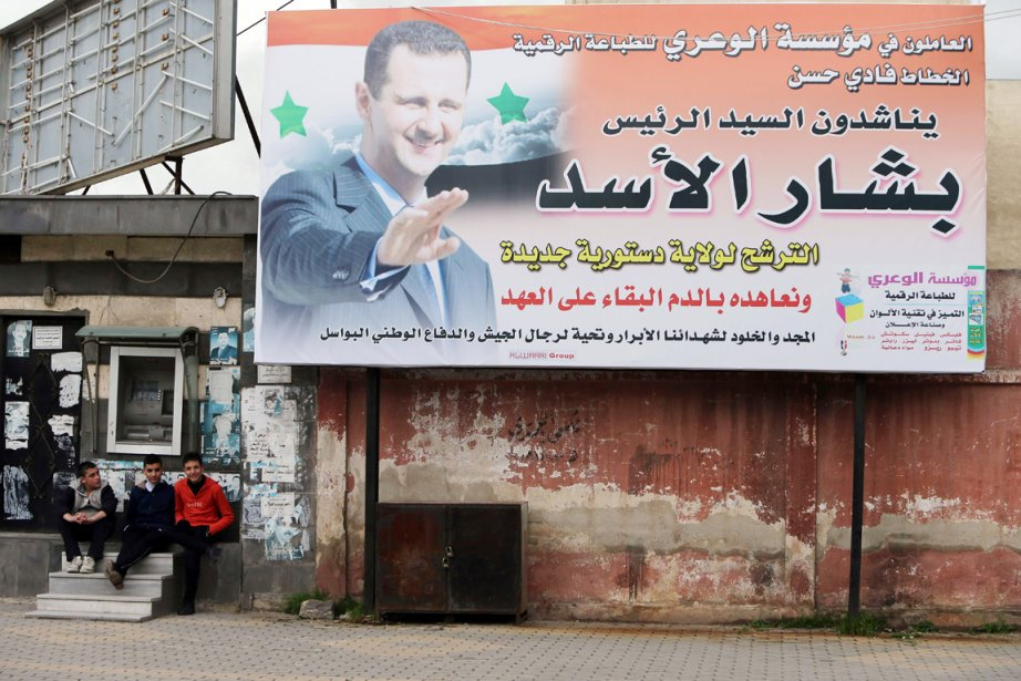 Des adolescents sont assis à côté d'une affiche... (PHOTO JOSEPH EID, AFP)
