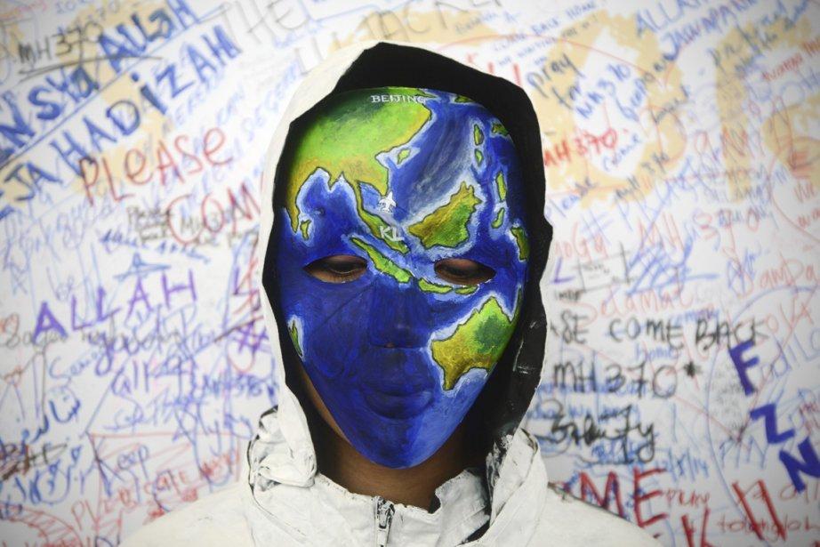 Une femme portant un masque peint aux couleurs... (PHOTO JOSHUA PAU, AP)