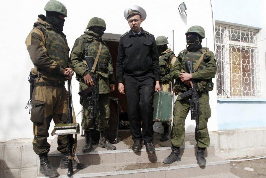 Un officier ukrainien passe devant des hommes armés... (PHOTO REUTERS)