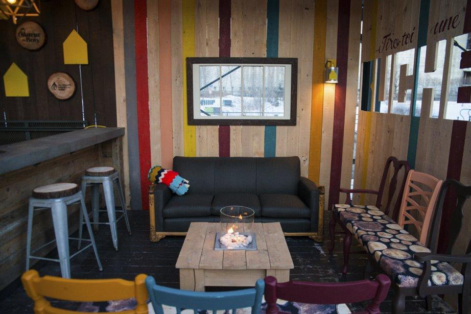 Dans le salon extérieur de La Cabane, des banquettes recouvertes d'un tissu à motifs de rondin ont été fabriquées avec d'anciennes chaises peintes de différentes couleurs. Les mêmes teintes illuminent les murs composés de planches. (Photo fournie par Simon Lebrun)