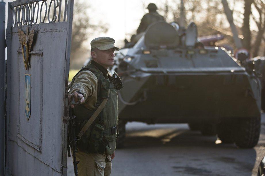 Un soldat pro-russe devant un blindé bloquant l'entrée... (Photo Vadim Ghirda, AP)
