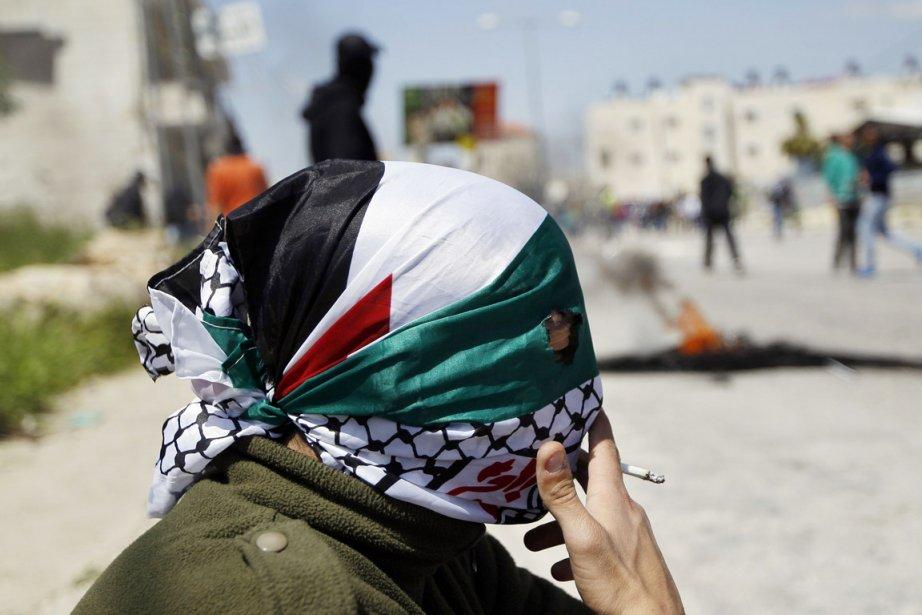 Un activiste le visage recouvert par le drapeau... (PHOTO MOHAMAD TOROKMAN, ARCHIVES REUTERS)