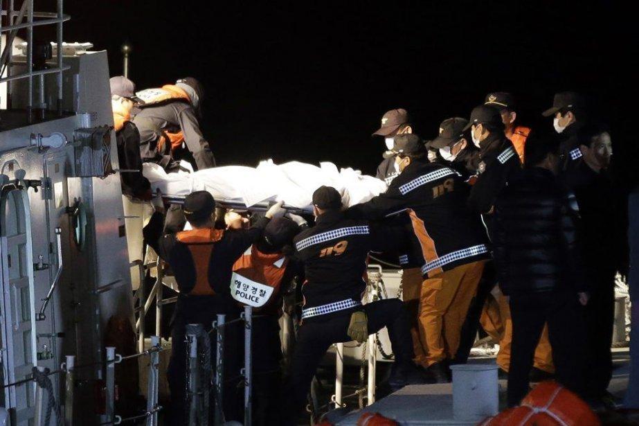 Des sauveteurs transportent le corps d'une victime du... (PHOTO LEE JIN-MAN, AP)
