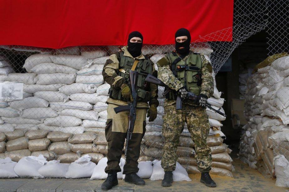 Des pro-russes armés montent la garde devant une... (Photo Sergei Grits, AP)