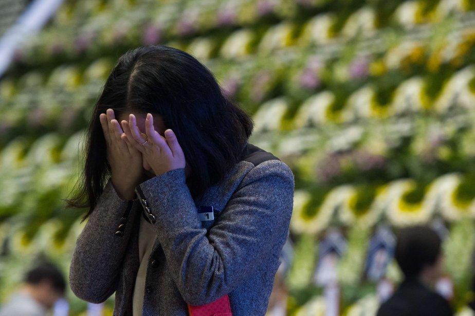 Les personnes défilent, souvent en pleurs, une fleur... (Photo KIM DOO-HO, AFP)
