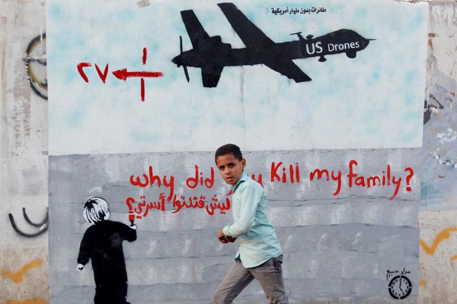 Un jeune garçon marche devant une affiche dénonçant... (PHOTO MOHAMMED HUWAIS, ARCHIVES AFP)
