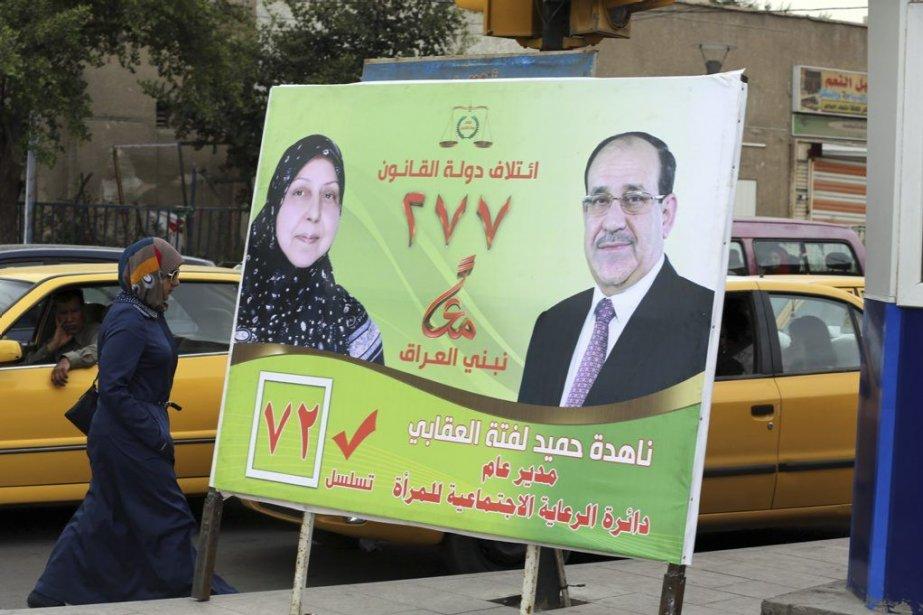 Une femme passe devant une affiche dupremier ministre... (PHOTO KARIM KADIM, AP)