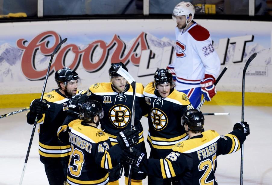 Les joueurs des Bruins festoient après un but compté en première période. En arrière-plan, Thomas Vanek la mine basse. (Photo Bernard Brault, La Presse)