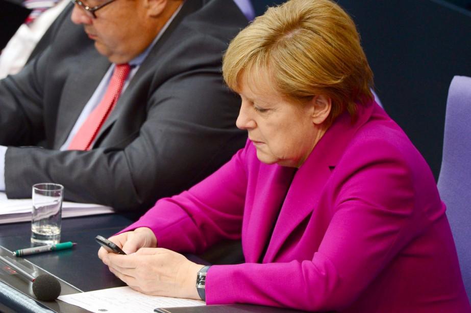 La chancelière Angela Merkel utilise son téléphone portable... (PHOTO JOHN MACDOUGALL, AFP)