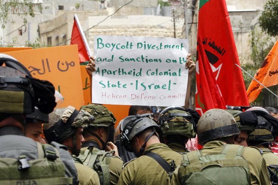 Un homme brandit une pancarte où il appelle... (PHOTO MUSSA QAWASMA, REUTERS)