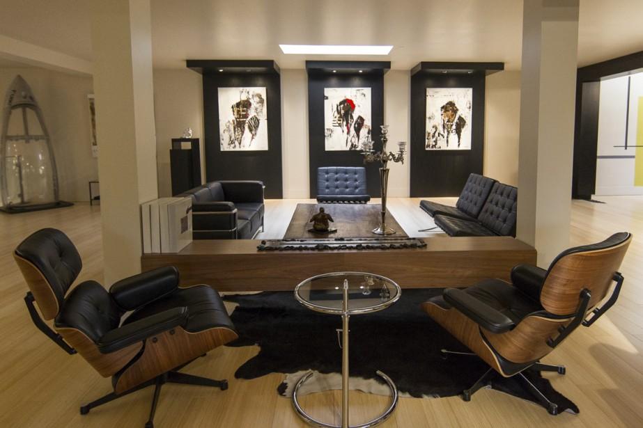 Pour séparer un coin conversation d'un autre, l'ébéniste maison a construit un meuble qui contient le foyer à l'éthanol. Au fond, à gauche, un cockpit d'avion à réaction fait décoration : une facétie de l'artiste. Mais les meubles choisis sont des classiques : Eames, Le Corbusier, Mies van der Rohe. (Photo Olivier Pontbriand, La Presse)