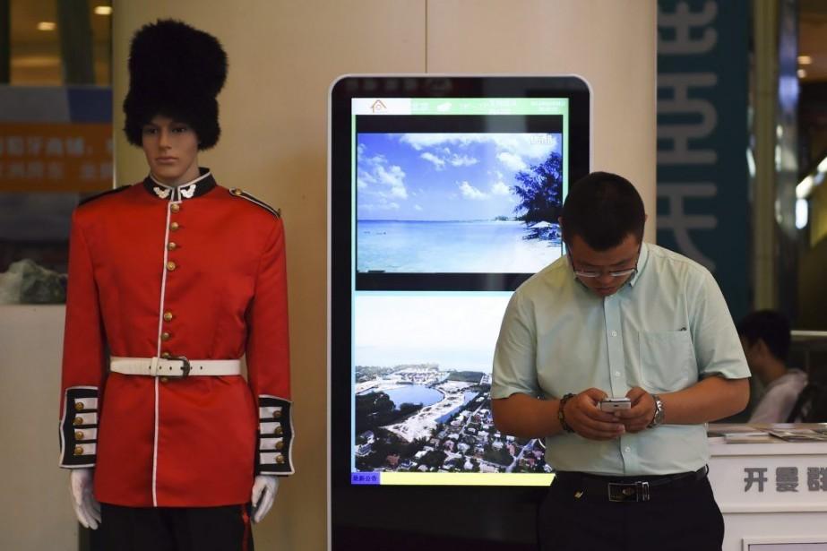 Un homme utilise son téléphone dans un centre... (PHOTO GREG BAKER, AFP)