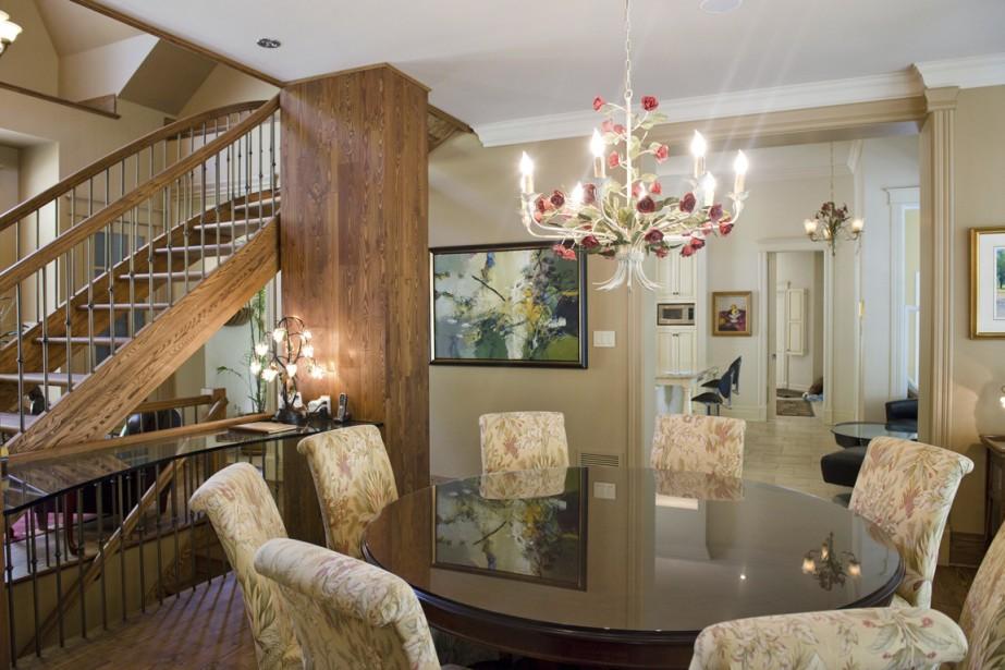 On constate l'enfilade de pièces à partir de la salle à manger. Au loin, on voit les tabourets de la cuisine; sur le côté, l'entrée avec son escalier menant à la petite mezzanine et à l'étage inférieur, où se trouvent des chambres d'ami, une salle de jeu et une cave à vin. (Photo STÉPHANIE MANTHA, LA VOIX DE L'EST)
