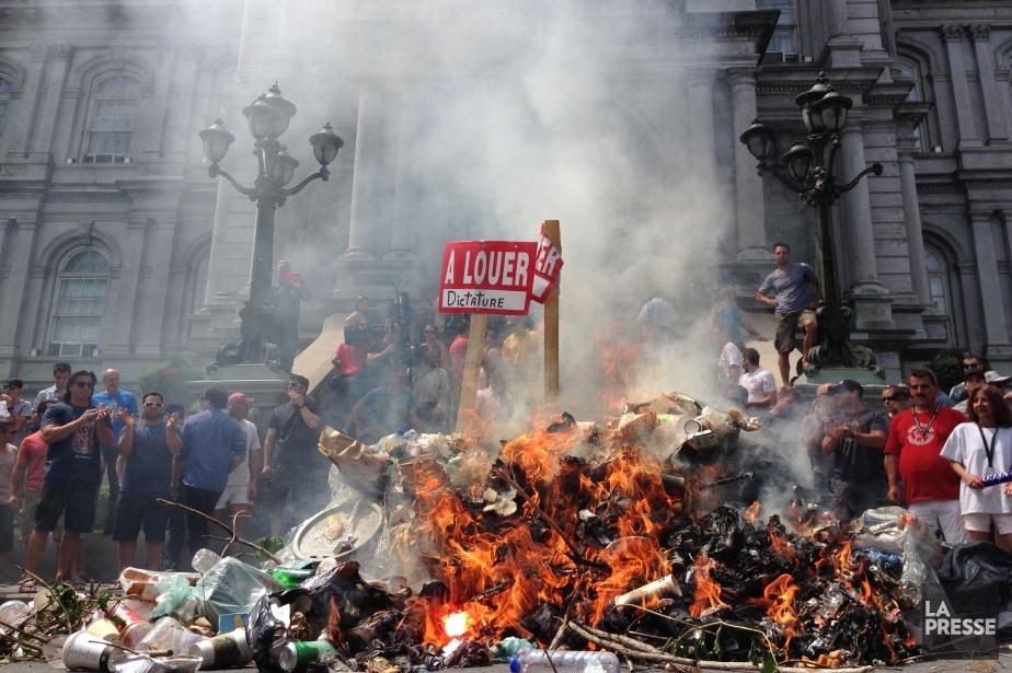 À Montréal, environ un millier de syndiqués de plusieurs services ont allumé un feu sur la rue Notre-Dame, devant l'hôtel de ville, alimenté notamment par des chemises et casquettes de pompiers. (Photo Patrick Sanfaçon, La Presse)