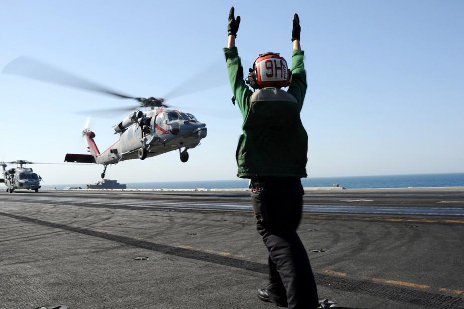 Un contrôleur dirige le décollage d'un hélicoptère MH-360... (PHOTO ARCHIVES AFP/MARINE AMÉRICAINE)