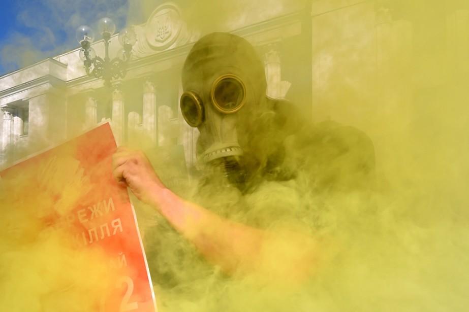 Un militant écologiste porte un masque à gaz en brandissant une pancarte où est écrit « Sauvons l'environnement, votons la loi 4972 », tandis que des manifestants allument des fumigènes devant le parlement ukrainien à Kiev. | 20 juin 2014
