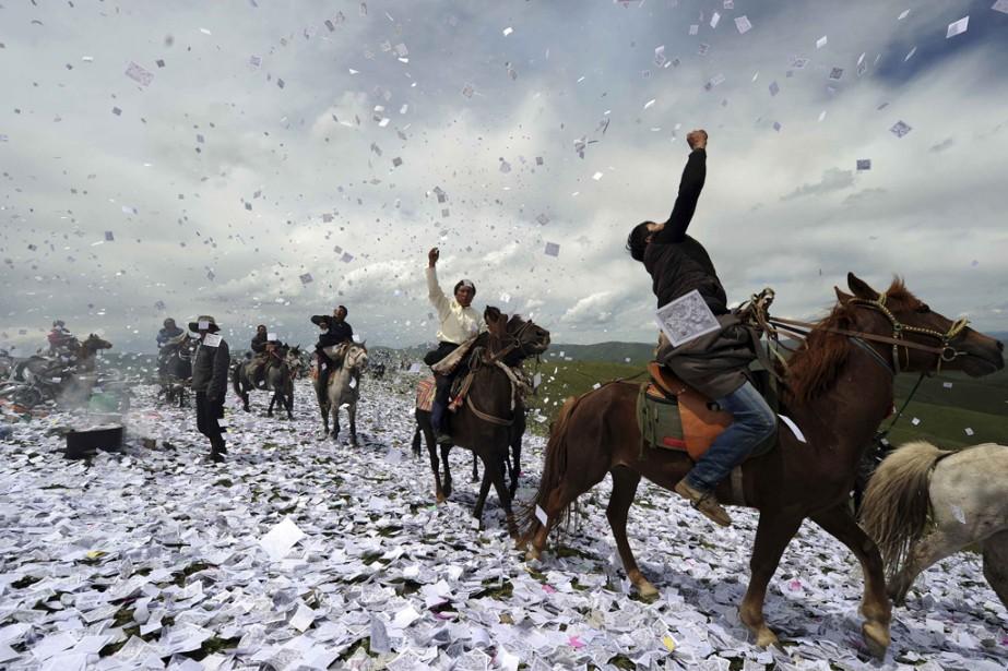 Dans la province du Sichuan, des cavaliers tibétains lancent des papiers ornés de prières pour attirer la chance, à l'occasion du festival Wei Sang. | 20 juin 2014
