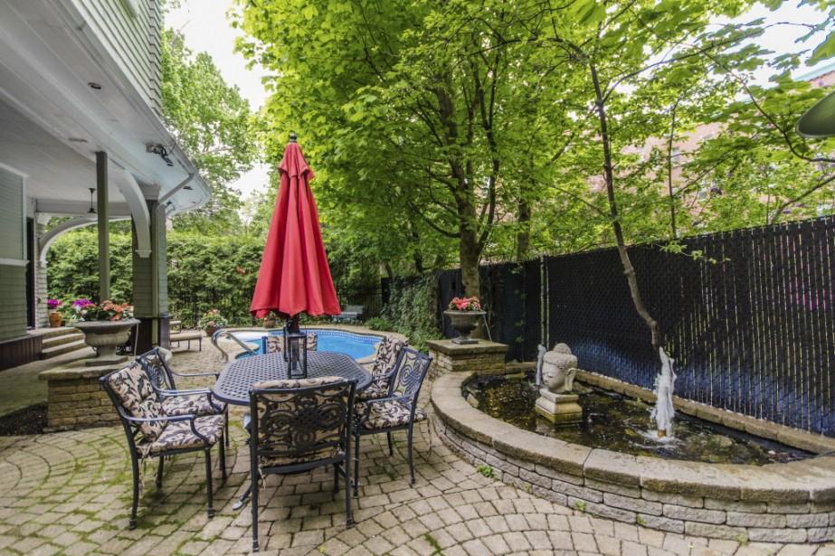 Aucun espace n'est laissé en plan: bassin avec jet deau, coin repas dallé, piscine sinueuse, barbecue toujours à l'abri, arbres matures. Avec le clapotis de l'eau et l'abondante végétation, on a l'impression d'être à la campagne. (Photo fournie par Sothebys International Realty Québec)