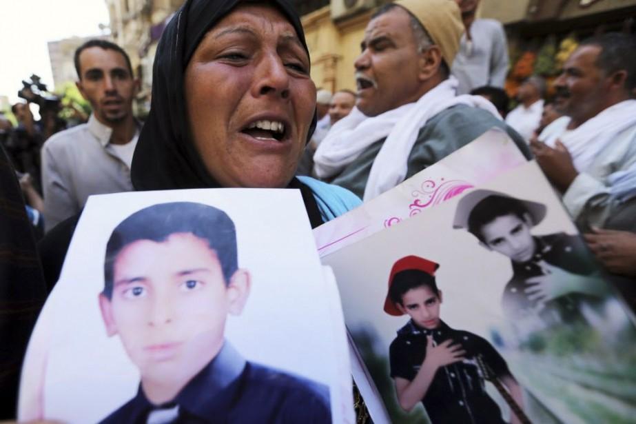 Une femme tient les photos de son fils,... (Photo MOHAMED ABD EL GHANY, Reuters)