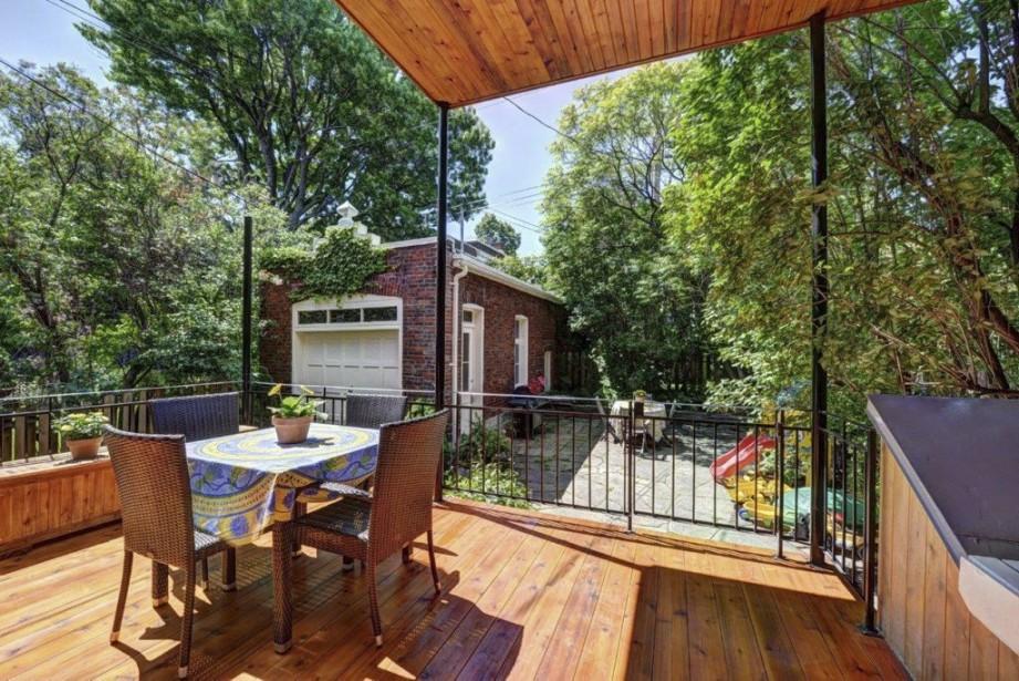La terrasse, en partie couverte, est baignée de soleil, ce qui la rend populaire en été. Les enfants peuvent jouer dans cette cour en sécurité, car elle est bien clôturée. L'ancien garage sert maintenant au rangement et la porte du poulailler, n'a plus de poules à accommoder! (PHOTO RE/MAX DU CARTIER)
