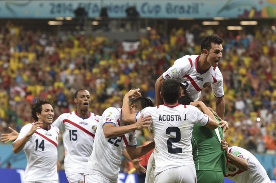 Les joueurs du Costa Rica célèbrent à la... (PHOTOARIS MESSINIS, AFP)