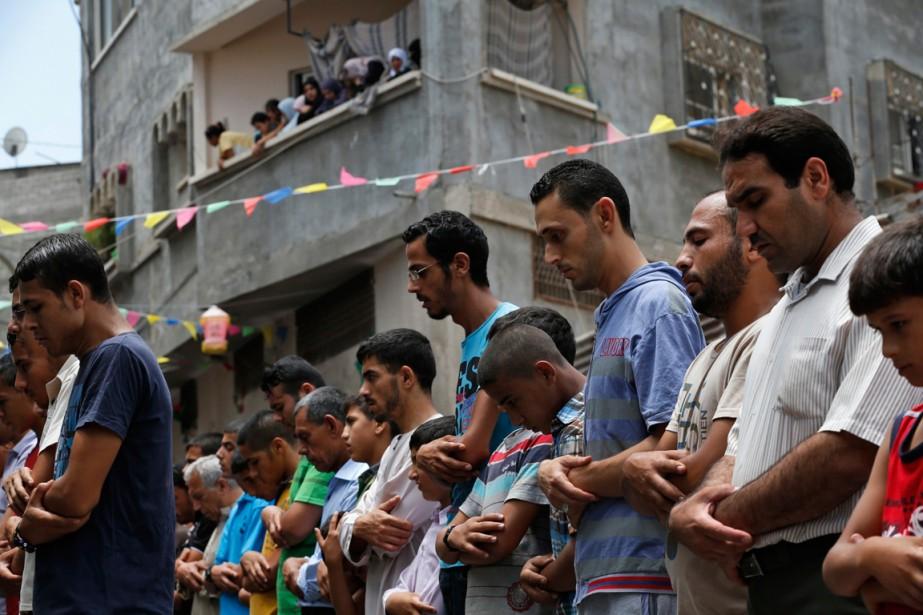 À Gaza, des Palestiniens prient pendant les funérailles... (Phoot Lefteris Pitarakis, Associated Press)