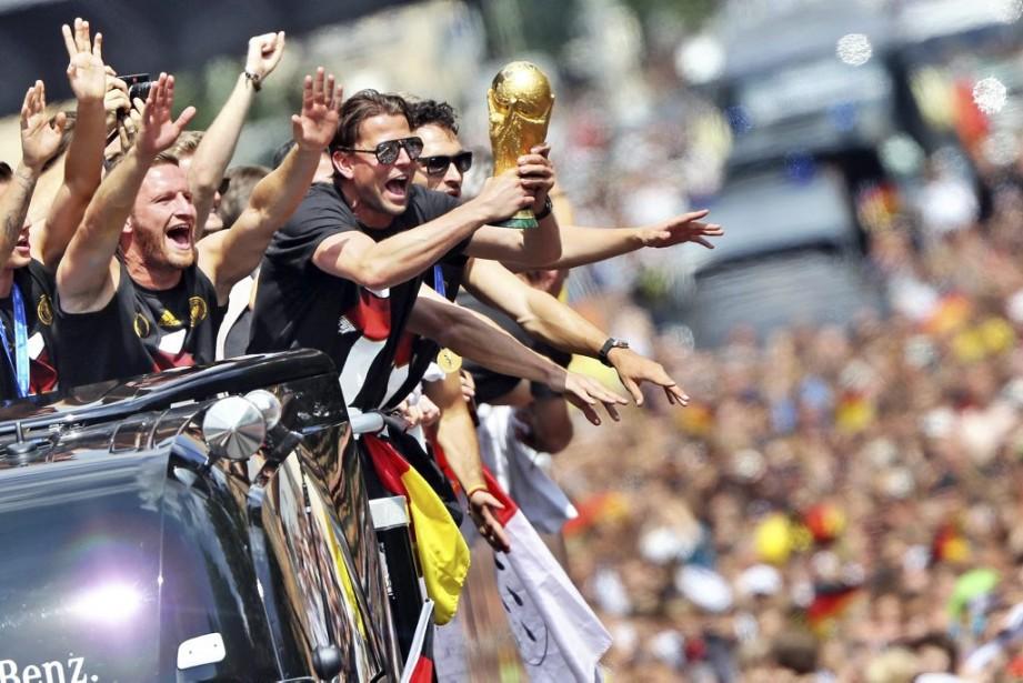 L'équipe allemande championne de la Coupe du monde de soccer a célébré le triomphe d'un quatrième titre pour le pays avec des centaines de milliers d'amateurs, mardi, en défilant avec le trophée à Berlin. (Photo Jan Woitas, AFP)