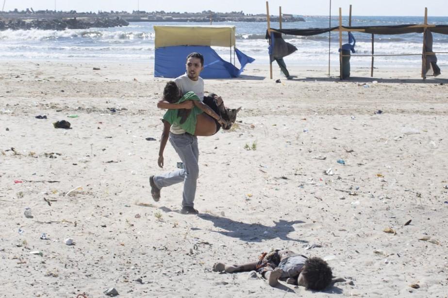 Un homme porte un enfant tandis qu'un autre... (PHOTO TYLER HICKS, THE NEW YORK TIMES)