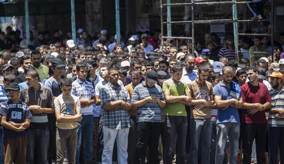 Des Palestiniens se recueillent au cours des funérailles de trois jeunes hommes morts en raison des bombardements.   17 juillet 2014