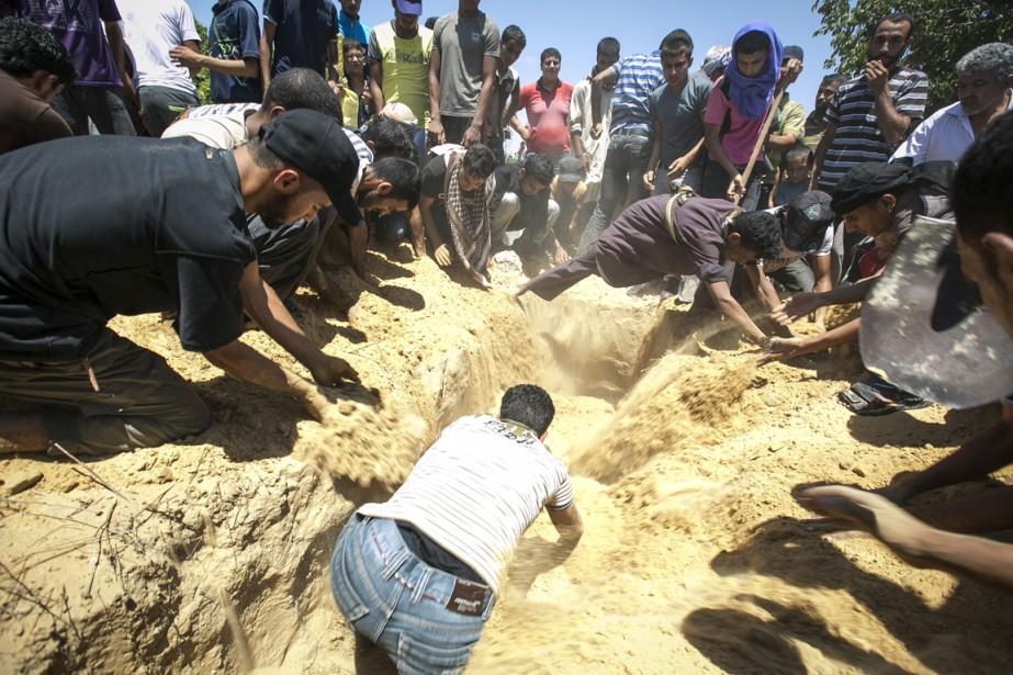 Des proches de Mohammed Sabri Hamad Abou al-Dbeir assistent à l'enterrement.   17 juillet 2014