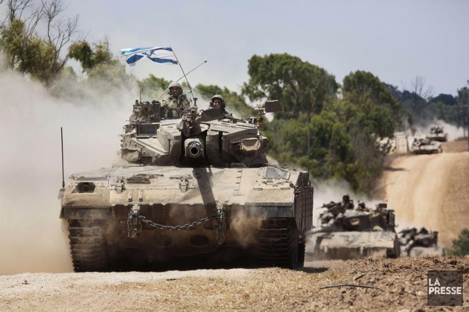 Un convoi de l'armée israélienne traverse la frontière... (PHOTO MENAHEM KAHANA, AFP)