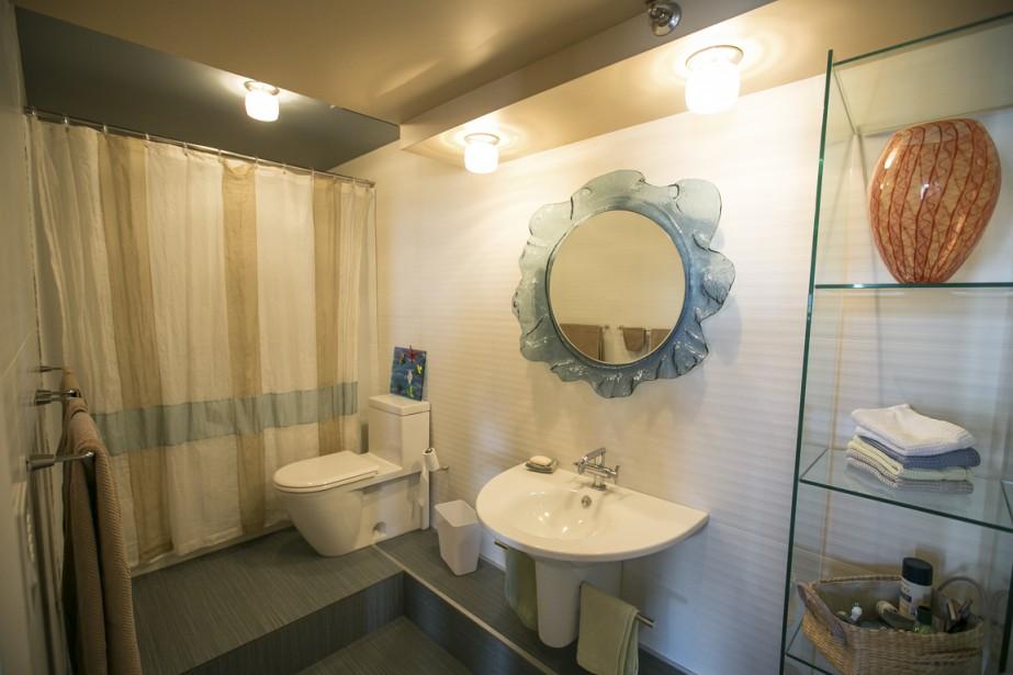 La salle de bains a été rénovée à l'arrivée des nouveaux propriétaires, mais elle a conservé sa configuration d'avant afin d'éviter les problèmes de tuyauterie. Elle arbore aujourd'hui une céramique de 24 x 24 po et donne la vedette au verre. (PHOTO OLIVIER PONTBRIAND, LA PRESSE)