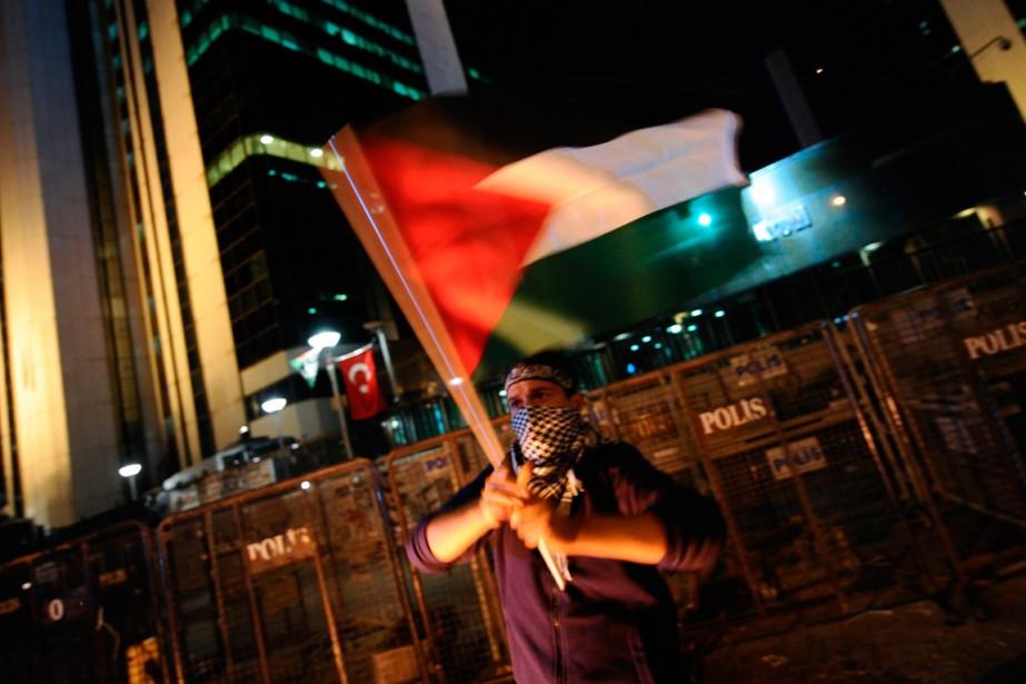 Un manifestant brandit un drapeau palestinien devant le... (PHOTO OZAN KOSE, AGENCE FRANCE-PRESSE)